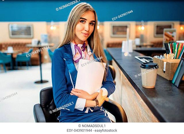 Stewardess sits at the bar counter in airport cafe. Air hostess drinks coffee in departure area, flight attendant in waiting zone, aviatransportations job