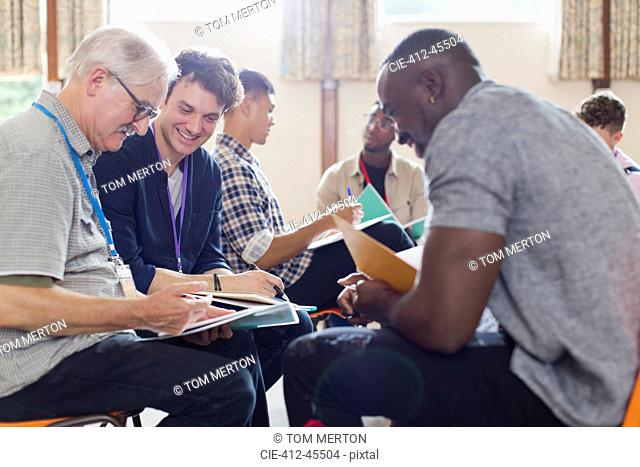 Men reading paperwork in group therapy in community center