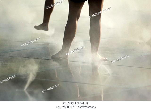 Young people dancing on tiles in the mist
