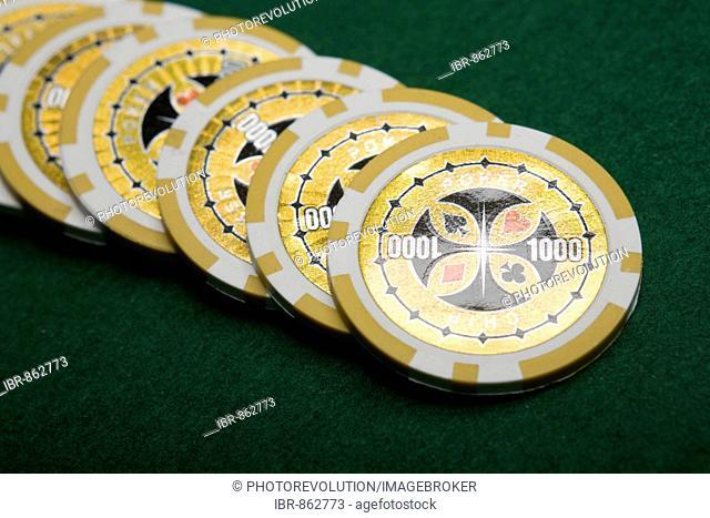 Yellow poker chips on green felt