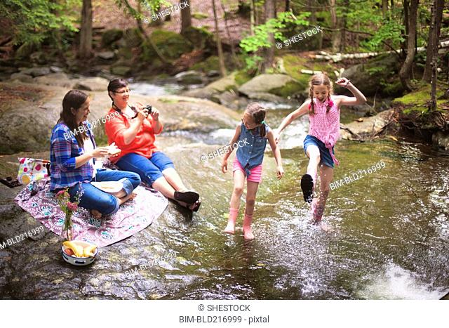 Three generations of Caucasian women playing in river
