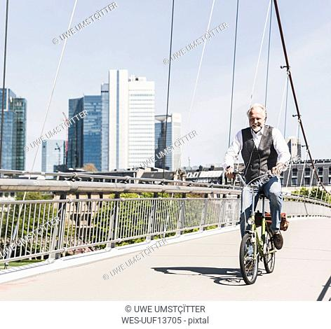 Smiling mature man on bicycle crossing bridge in the city