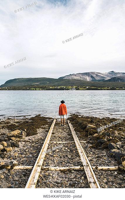 Northern Norway, Man standing alone at fjord, looking at view