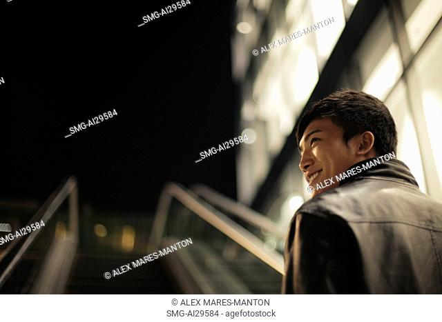Rear view of young man going up an escalator at night