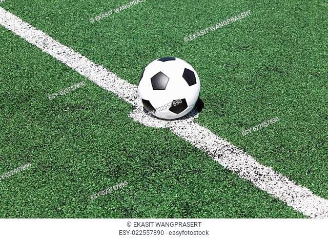 soccer ball on white line in green grass