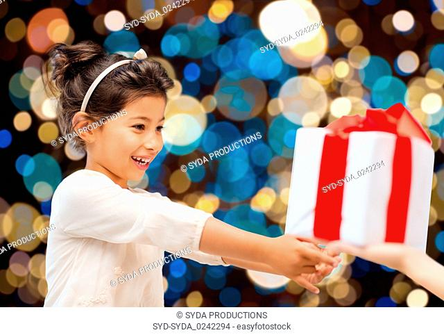 smiling little girl giving or receiving present