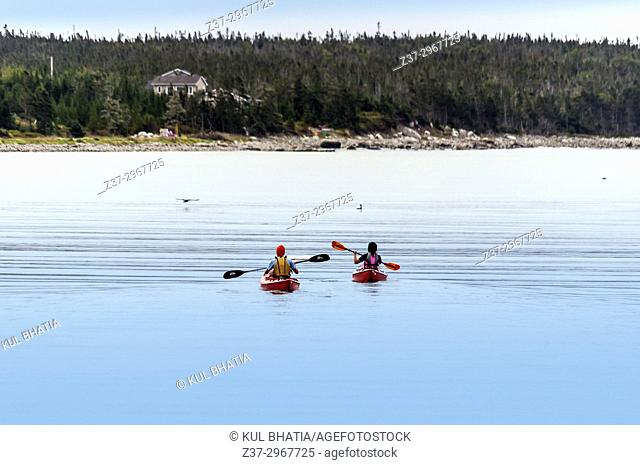 Two kayakers, a man and a woman, paddle their kayaks in a cove of the Atlantic Ocean, Halifax, Nova Scotia