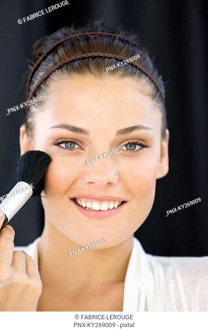 Portrait of a woman applying blusher on her face