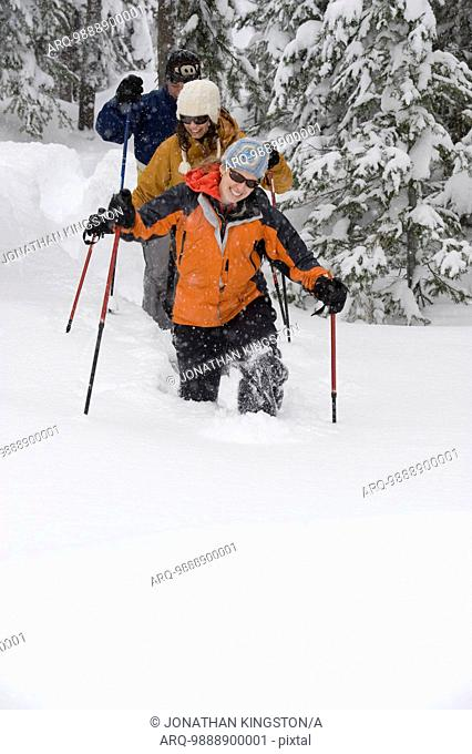 Front view of three people snowshoeing in the woods in deep powder in Bend, Oregon