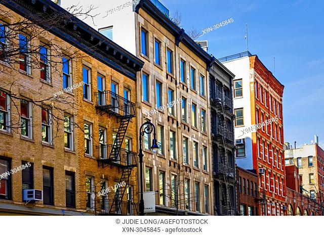 Manhattan, New York City, Soho, Looking Up at Tenement Apartment Buildings, one traditional with fire escapes, one updated with modern windows