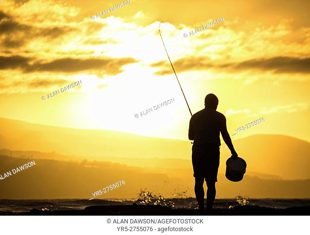 A man fishing at sunset at El Confital bay, Las Palmas, Gran Canaria, Canary Islands, Spain