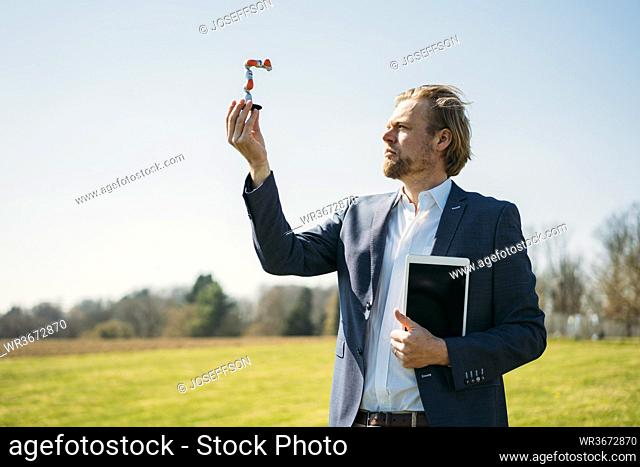 Businessman analyzing at small robotic arm while holding digital tablet against clear sky during sunny day