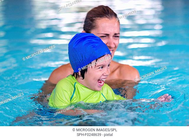 Boy in swimming pool with mother