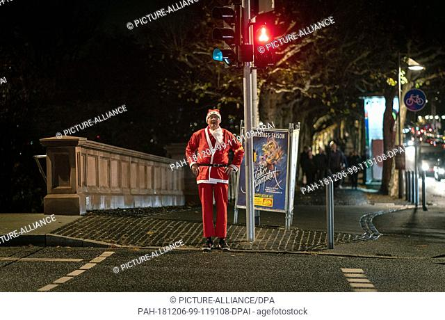 06 December 2018, Hessen, Frankfurt/Main: A jogger disguised as Santa Claus stands at a red traffic light in the evening. Photo: Frank Rumpenhorst/dpa