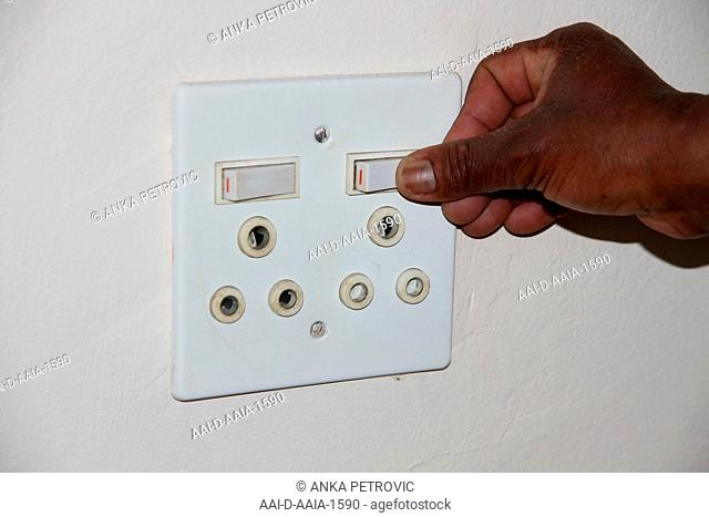Close-up of hand pressing a white double power socket, South Africa