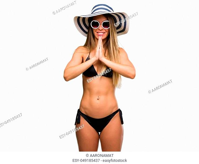 Beautiful young woman wearing bikini, sunglasses and hat praying with hands together asking for forgiveness smiling confident