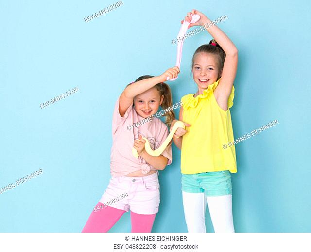 two beautiful girls playing with homemade slime and having a lot of fun