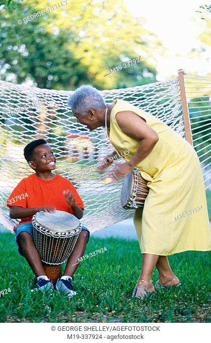Gandmother and grandson playing african drums
