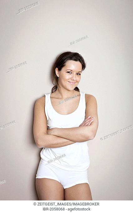 Young woman with a friendly smile, wearing underwear, crossed arms, leaning against a wall