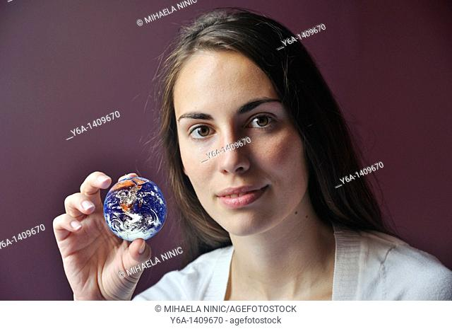 Young woman holding planet earth