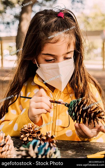 Cute girl wearing protective face mask while coloring pine cone at table in park