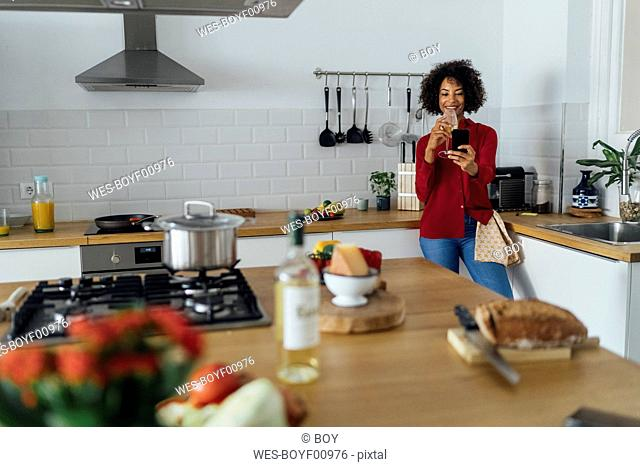 Woman standing in her kitchen, taking a selfie, drinking wine