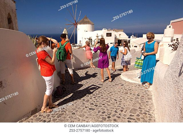 Tourists taking photos in front of the traditional windmill in Oia village, Santorini, Cyclades Islands, Greek Islands, Greece, Europe