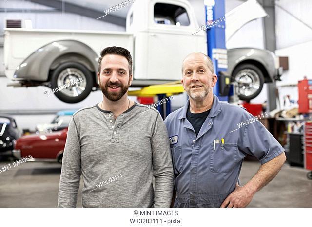 A portrait of a Caucasian senior car mechanic and his son in their classic car repair shop