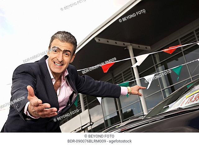 portrait of salesman at car dealer gesturing
