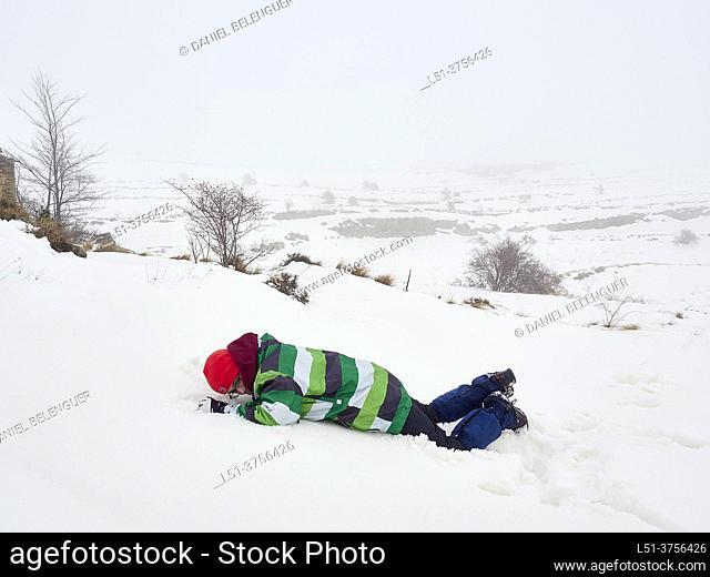Boy (teenager) walking on the snow, countryside near Puertomingalvo, Teruel, Spain