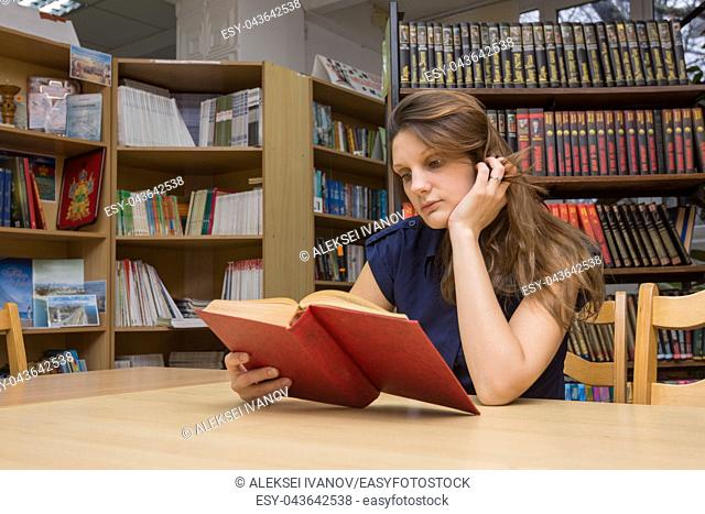 A library visitor reads a book in a library