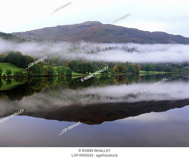Engalnd, Cumbria, Grasmere, Early morning reflections and mist on Grasmere. Grasmere is probably the Cumbria's most popular village