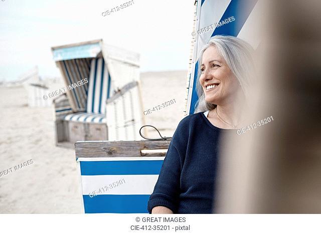Smiling senior woman looking away on beach