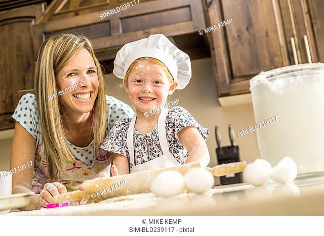 Caucasian mother and daughter covered in flour from food fight