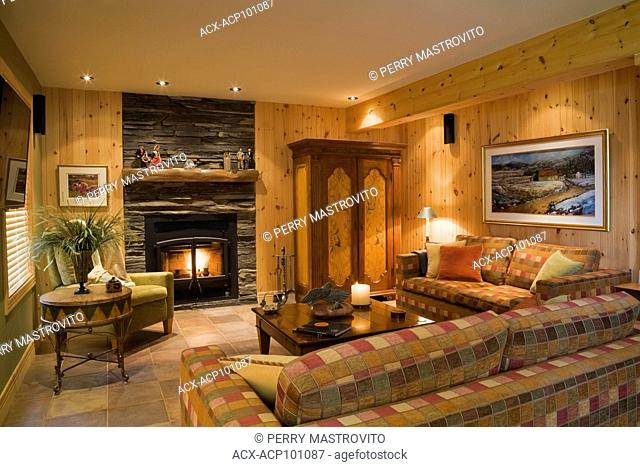 Family room with lit fireplace in the basement inside a handcrafted spruce log home, Quebec, Canada. This image is property released. CUPR0280