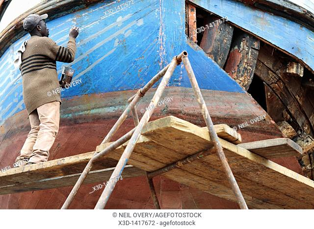 Workman painting repaired hull of wooden fishing boat in a dry dock, Hout Bay, Western Cape, South Africa