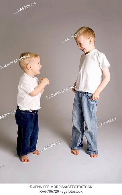 Two blond haired brothers, 6 and 3 years old, wearing white t-shirts and blue jeans, look at each other and laugh, sharing a joke