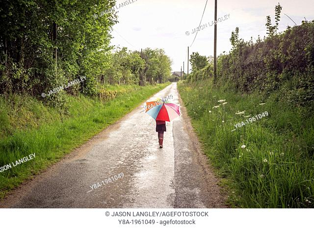 A young girl walking in the rain carrying an umbrella, La Creuse, Limousin, France