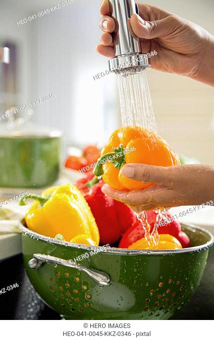 Woman using sprayer hose on peppers in kitchen sink