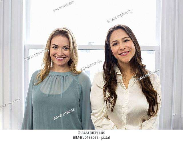 Caucasian businesswomen smiling near window