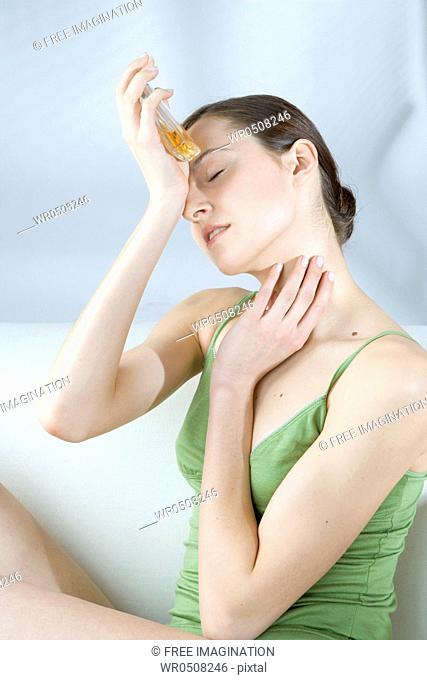 woman smelling perfume on wrist