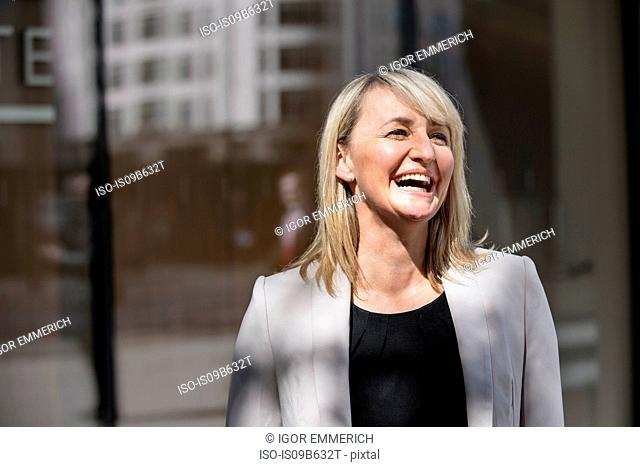 Businesswoman in front of glass building, London, UK
