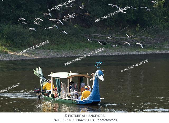 dpatop - 25 August 2019, Saxony, Dresden: Lay actors in baroque costumes ride in a baroque pleasure gondola on the Elbe. The 300th anniversary of the wedding of...