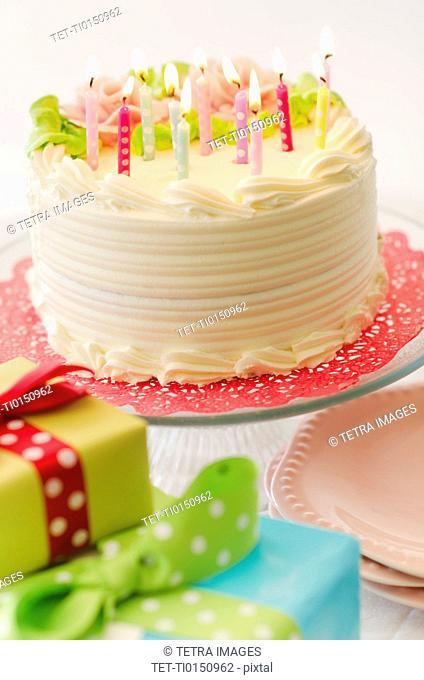 Studio shot of colorful birthday cake and birthday gifts