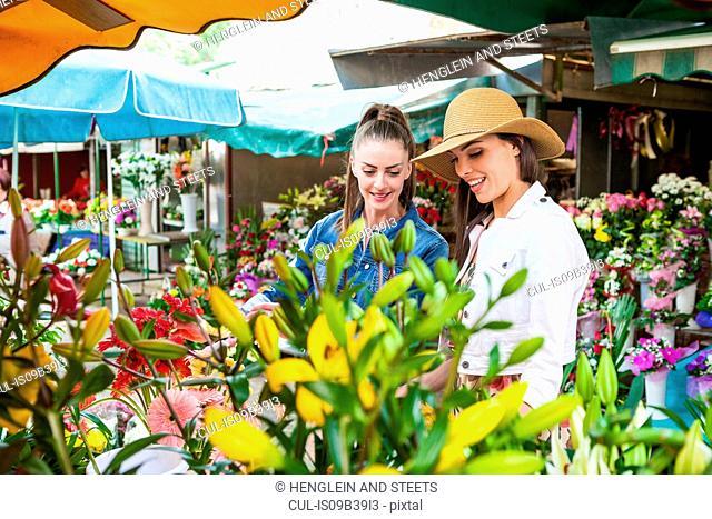 Young female tourist selecting flowers at market stall, Split, Dalmatia, Croatia