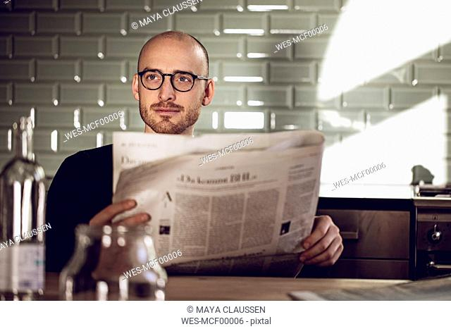 Man sitting in kitchen, reading newspaper