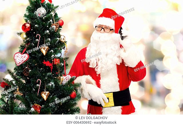 holidays, technology and people concept - man in costume of santa claus with smartphone and christmas tree over lights background