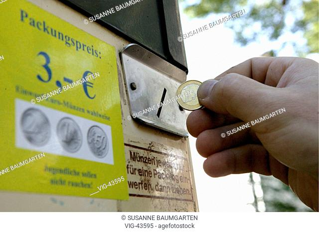 Hand putting a 1 Euro coin into a cigarette machine. Next to it a sign: box price 3 Euro - BONN, GERMANY, 24/09/2003