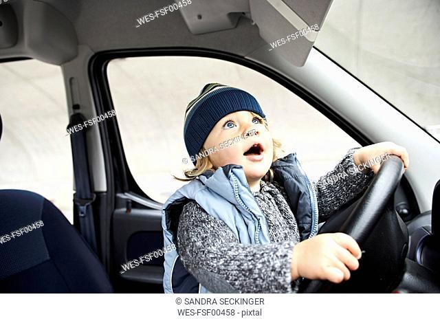 Little boy sitting at steering wheel of car