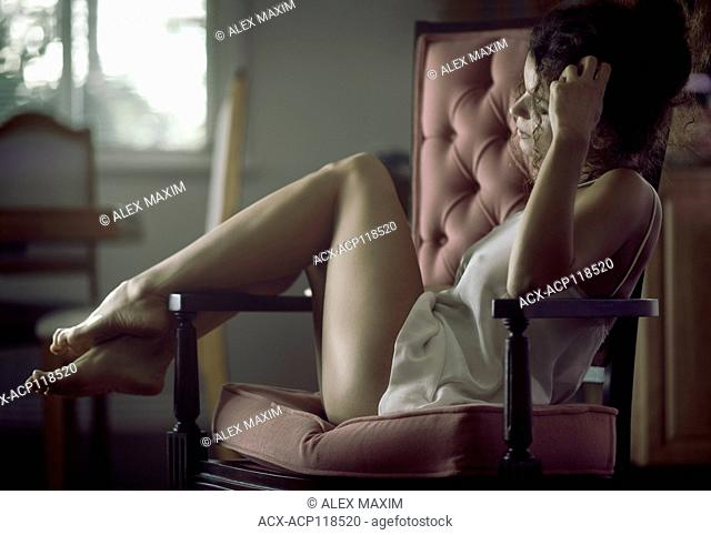 Sensual romantic portrait of a beautiful young woman in a night shirt sitting in an armchair with thoughtful expression